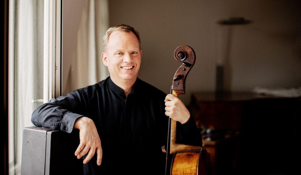 Christoph Stradner an altem Cellokasten lehnend