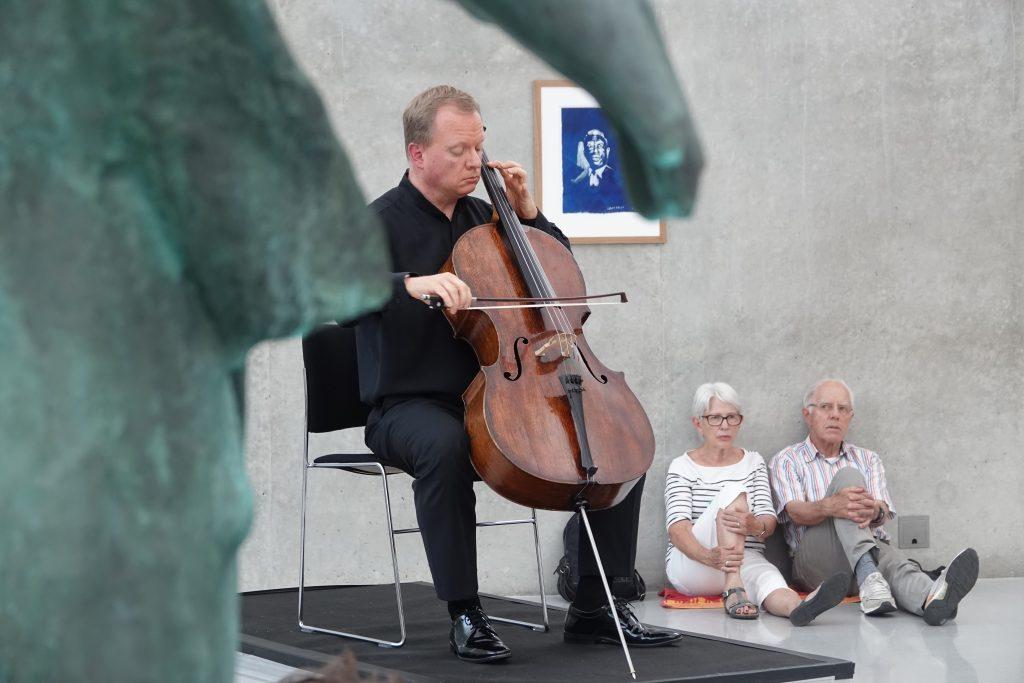 Bachsuiten, im Hintergrund 2 ältere Personen am Boden sitzend